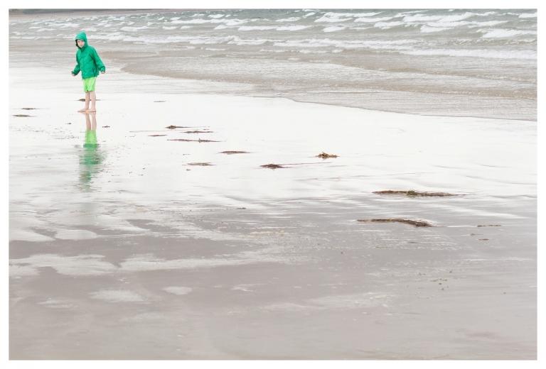 boy in green jacket on beach