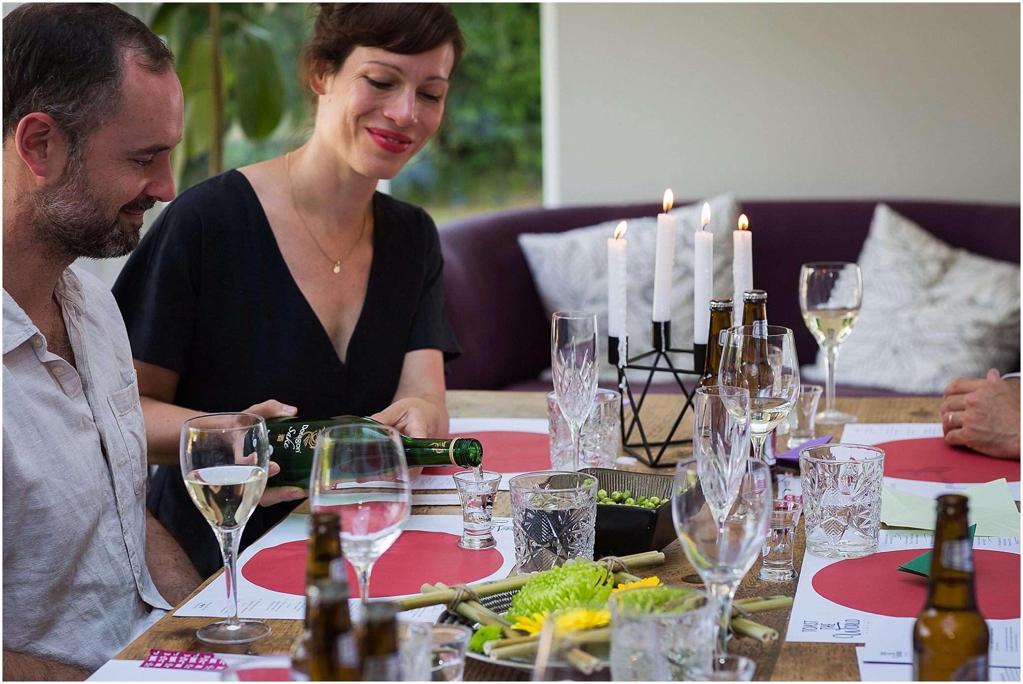 Woman pouring sake at dinner party